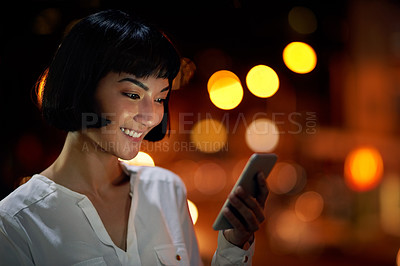 Buy stock photo Shot of an attractive young woman using a mobile phone outside in the city at night