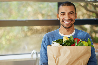 Buy stock photo Portrait of a happy young man holding a bag full of healthy vegetables at homee