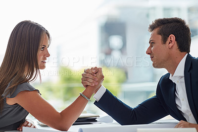 Buy stock photo Shot of two businesspeople arm wrestling in an office