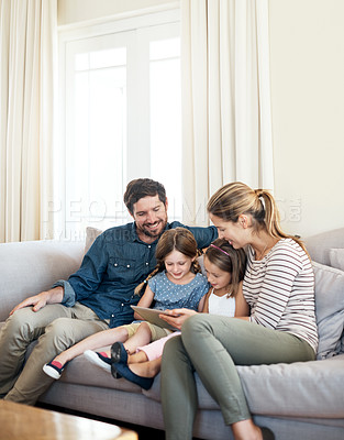 Buy stock photo Shot of two adorable sisters using a digital tablet together with their parents on the sofa at home