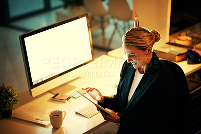 Buy stock photo Shot of a mature woman using her digital tablet while working late at the office