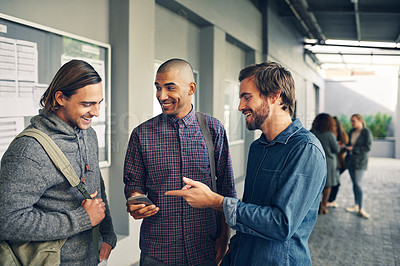 Buy stock photo Shot of a group of young students using a mobile phone together on campus