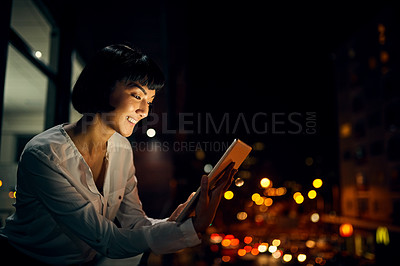 Buy stock photo Shot of an attractive young woman using a digital tablet outside in the city at night