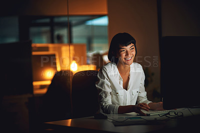 Buy stock photo Shot of a young businesswoman using a computer during a late night at work