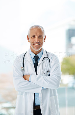 Buy stock photo Cropped shot of a mature male doctor standing with his arms crossed