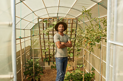 Buy stock photo Portrait of a young man standing in a greenhouse
