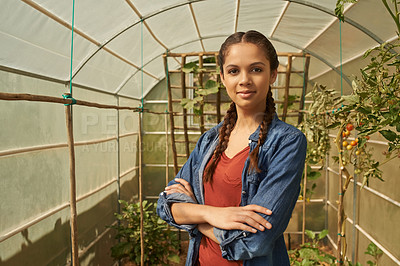 Buy stock photo Portrait of a young woman standing in a greenhouse