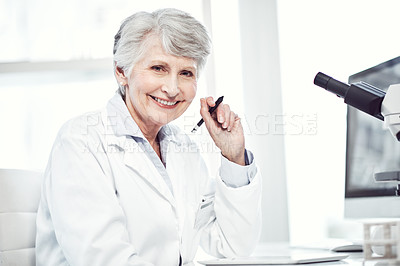Buy stock photo Portrait of a cheerful elderly female scientist making notes while looking at the camera and smiling in a laboratory