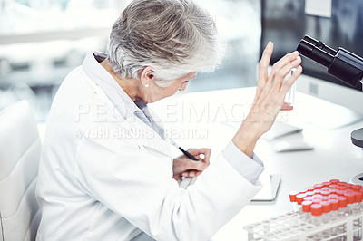 Buy stock photo Shot of a focused elderly female scientist holding up a test tube and examining it inside of a laboratory