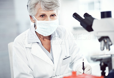Buy stock photo Portrait of a focused elderly female scientist making notes while looking into the camera and wearing a doctor's mask inside of a laboratory