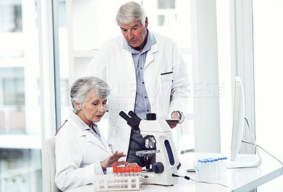 Buy stock photo Shot of two elderly and focused scientists working together inside of a laboratory