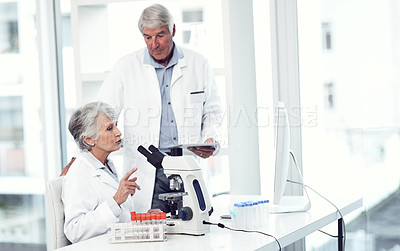 Buy stock photo Shot of two focused elderly scientists working together inside of a laboratory