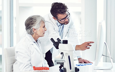 Buy stock photo Shot of two focused scientist working together on a computer inside of a laboratory