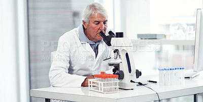 Buy stock photo Shot of a focused elderly male scientist looking through a microscope while being seated inside of a laboratory