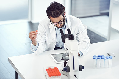 Buy stock photo Shot of a focused young male scientist making notes while holding up a test tube inside a laboratory