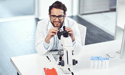 Buy stock photo Shot of a cheerful young male scientist looking through a microscope inside of a laboratory