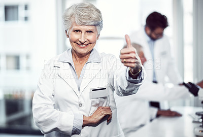 Buy stock photo Portrait of a cheerful elderly female scientist showing thumbs up while looking into the camera inside a laboratory