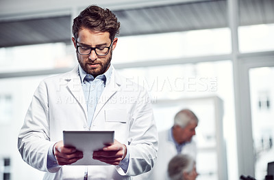 Buy stock photo Shot of a focused young male scientist using a digital tablet while standing inside of a laboratory