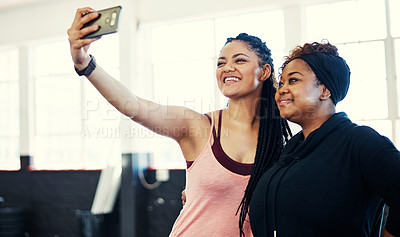 Buy stock photo Shot of two cheerful young women taking a self portrait together before a workout session in a gym