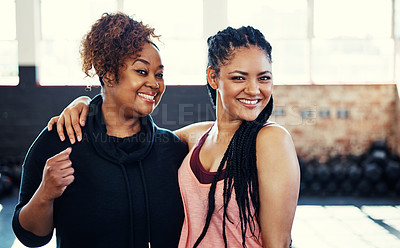 Buy stock photo Portrait of two cheerful young women having a conversation while looking into the camera before a workout session in a gym