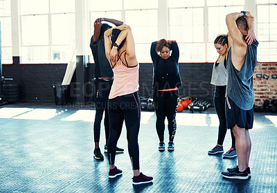 Buy stock photo Shot of a group focused young people standing in a circle and stretching before a workout session in a gym