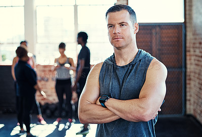 Buy stock photo Shot of a focused young man standing with arms folded while contemplating before a workout in a gym