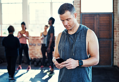 Buy stock photo Shot of a focused young man standing and using his cellphone before a workout in a gym
