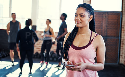 Buy stock photo Shot of a cheerful young woman standing and using her cellphone while contemplating before a workout in a gym
