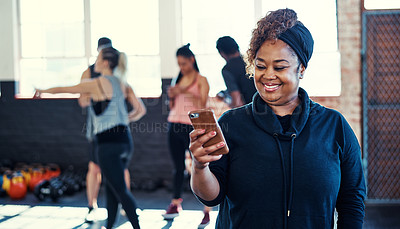 Buy stock photo Shot of a cheerful young woman standing and using her cellphone before a workout session in a gym