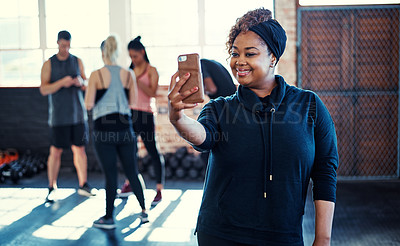 Buy stock photo Shot of a cheerful young woman standing and taking a self portrait with her cellphone before a workout in a gym