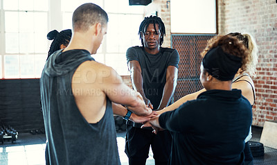 Buy stock photo Shot of a focused young group of people forming a huddle together before a workout session in a gym