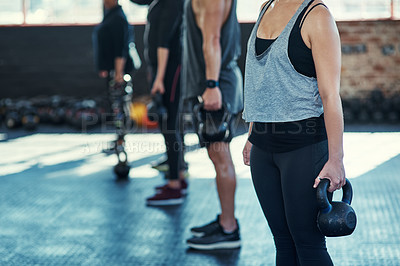 Buy stock photo Shot of a group unrecognizable people standing in a row doing training with weights in a gym