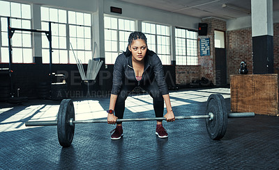 Buy stock photo Shot of a young woman lifting weights in a gym