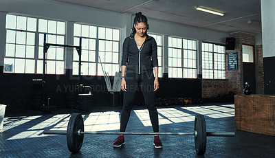 Buy stock photo Shot of a young woman getting ready to lift weights in a gym