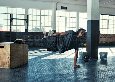 Buy stock photo Shot of a young man doing a side plank with a wooden block in a gym