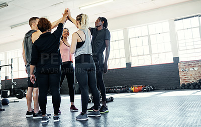 Buy stock photo Shot of a cheerful young group of people forming a huddle together before a workout session in a gym