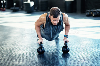 Buy stock photo Shot of a young man doing push ups with kettlebells in a gym