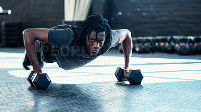 Buy stock photo Shot of a young man doing push ups with dumbbells in a gym