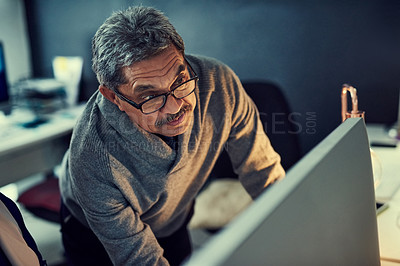 Buy stock photo Shot of a mature businessman working late in an office