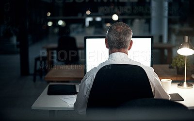 Buy stock photo Rearview shot of an unrecognizable mature businessman working late in the office