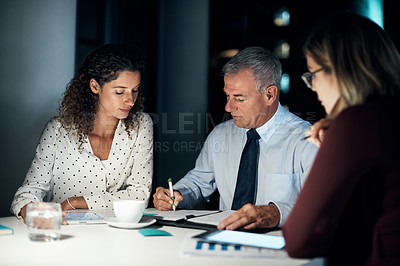 Buy stock photo Cropped shot of three business colleagues having a late night meeting at the office