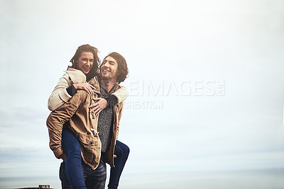 Buy stock photo Portrait of a affectionate young woman having a piggyback ride on her boyfriend's back while looking at the camera outside