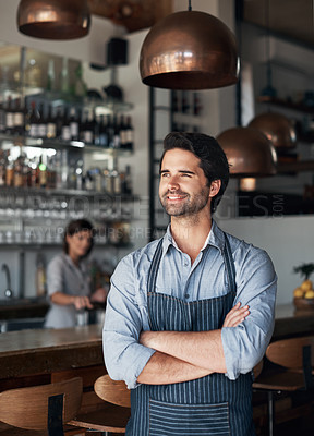 Buy stock photo Cropped shot of a handsome young man standing with his arms folded in his coffee shop