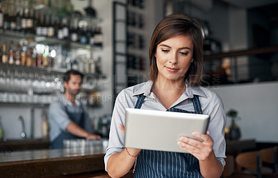 Buy stock photo Cropped shot of an attractive young woman using a tablet while working in her coffee shop