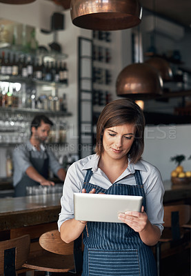 Buy stock photo Cropped shot of an attractive young woman working on a tablet while standing in her coffee shop