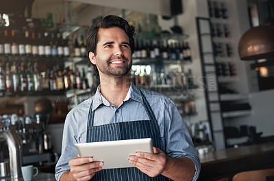 Buy stock photo Cropped shot of a handsome young man using a tablet while working in his coffee shop