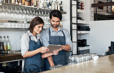 Buy stock photo Cropped shot of two young entrepreneurs using a tablet while working in their coffee shop