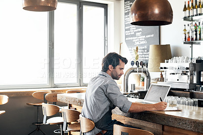 Buy stock photo Cropped shot of a handsome young man working on a laptop while sitting in his coffee shop
