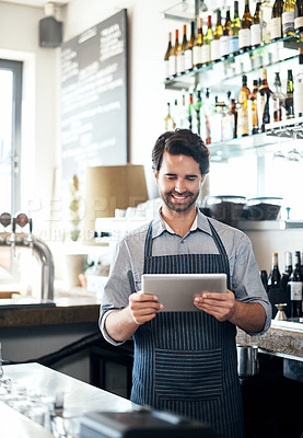 Buy stock photo Cropped shot of a handsome young man working on a tablet while standing in his coffee shop