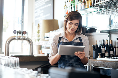 Buy stock photo Cropped shot of an attractive young woman using a tablet while standing in her coffee shop